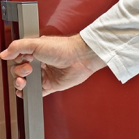 Hand on door handle of a red refrigerator