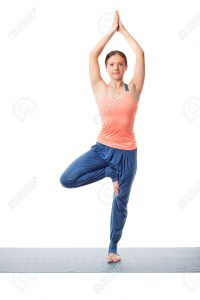 Beautiful sporty fit yogini woman practices yoga asana Vrikshasana - tree pose isolated on white